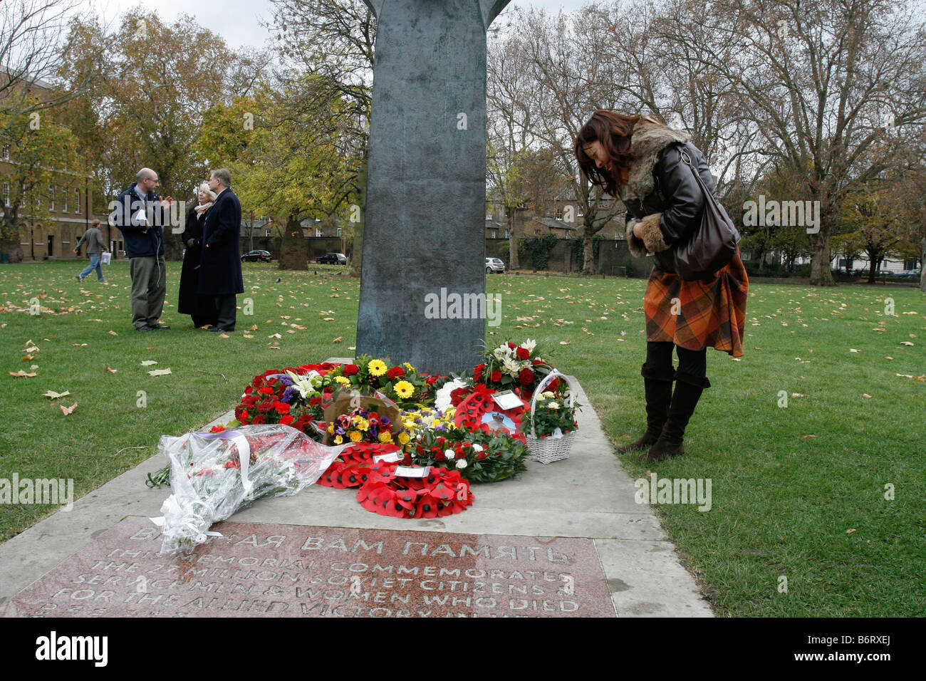 A lady looking at the Remembrance Day Tributes at the Soviet War Memorial, Central London. - Stock Image