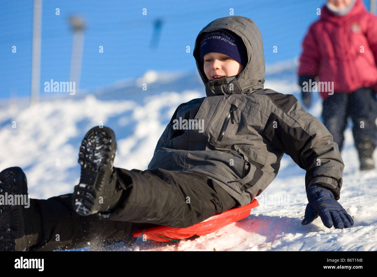 Brave little boy slides on plastic bob from hillside with high speed Stock Photo