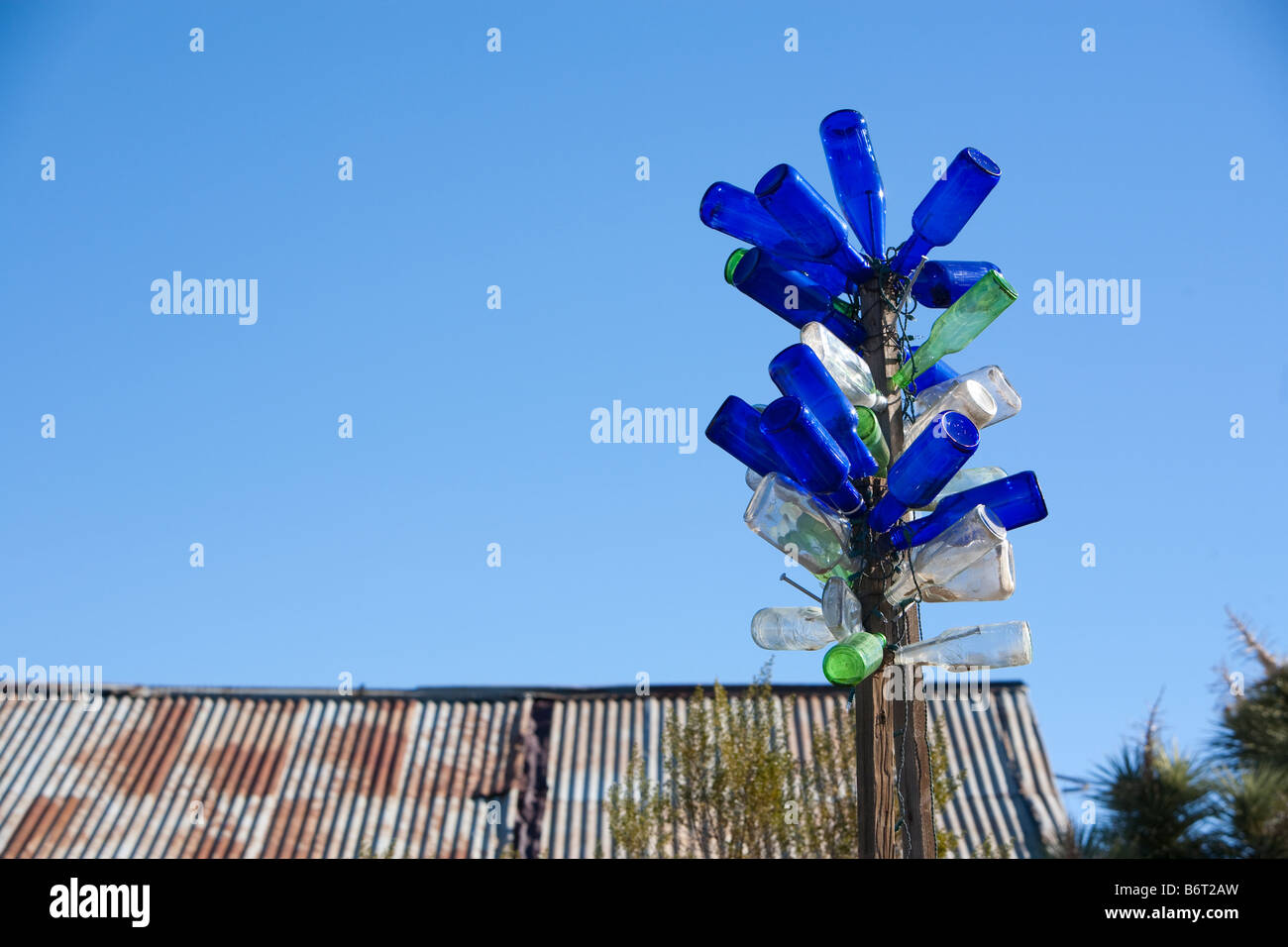 An artist's creation of a sculpture made from old glass bottles is displayed on the top of a pole in Randsburg - Stock Image
