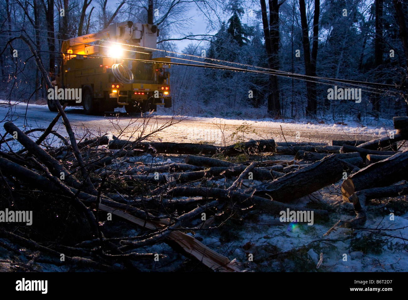 Utility truck lights a fallen tree in the roadway at dusk during winter - Stock Image