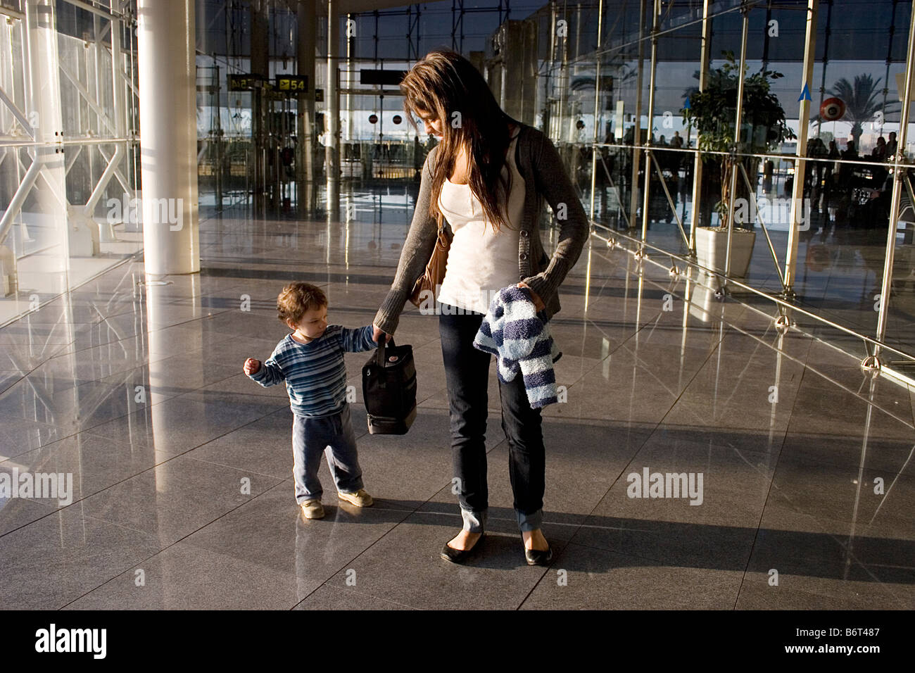 young mother arriving with toddler at european airport Stock Photo