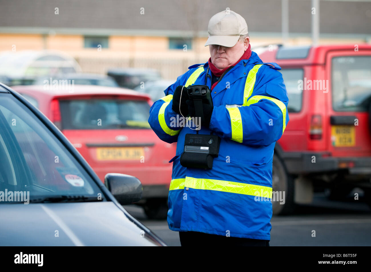 A private car park attendant wearing blue jacket taking the details of a car parked in his electronic notebook, Stock Photo