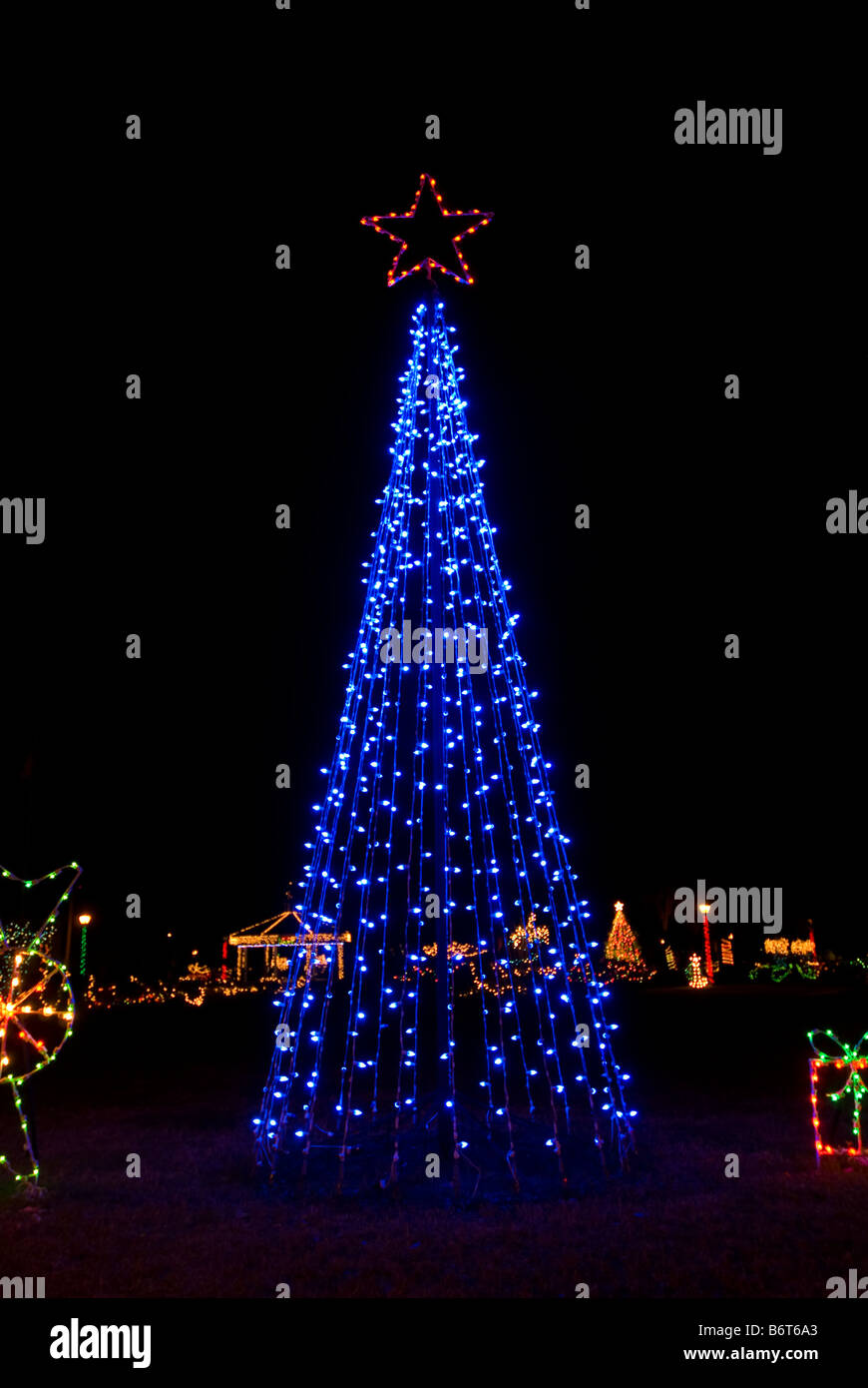 Christmas tree bright blue color lights night dark background christmas decorations decor dark background - Stock Image