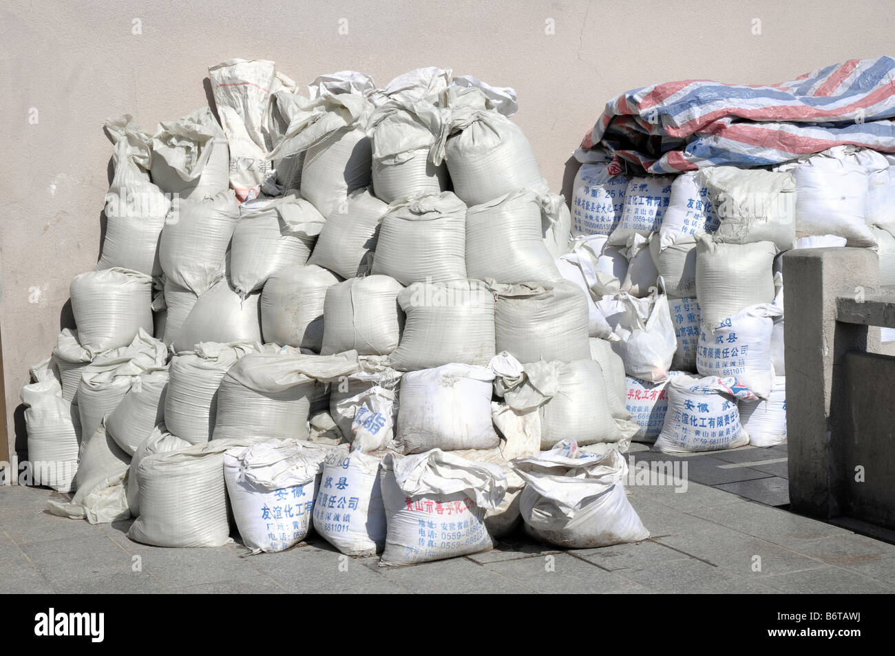 White sacks of supplies waiting to be taken up the mountain by porters. Huangshan, Yellow Mountain, Anhui, China. - Stock Image
