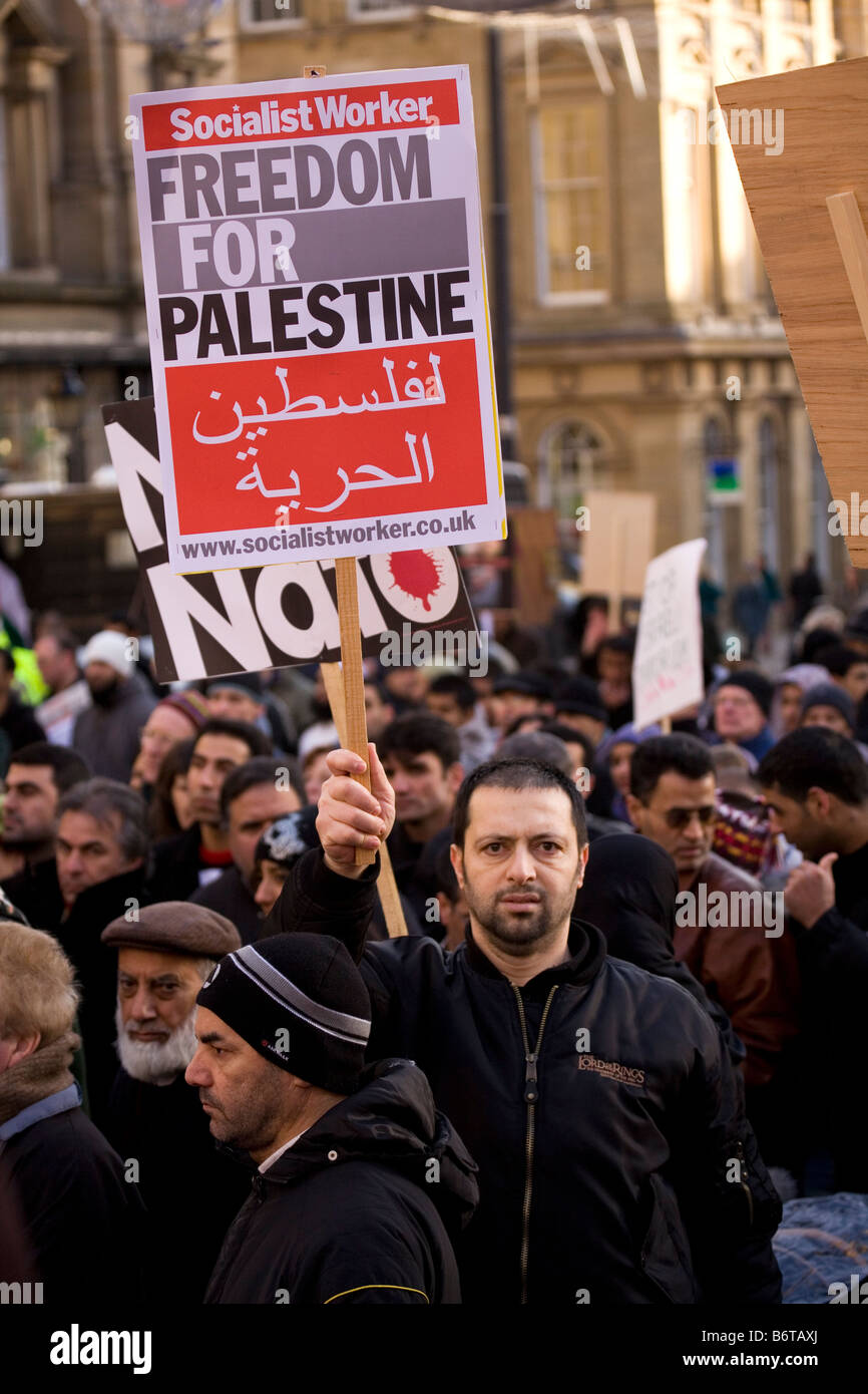A man holds aloft a placard calling for 'Freedom for Palestine'. - Stock Image