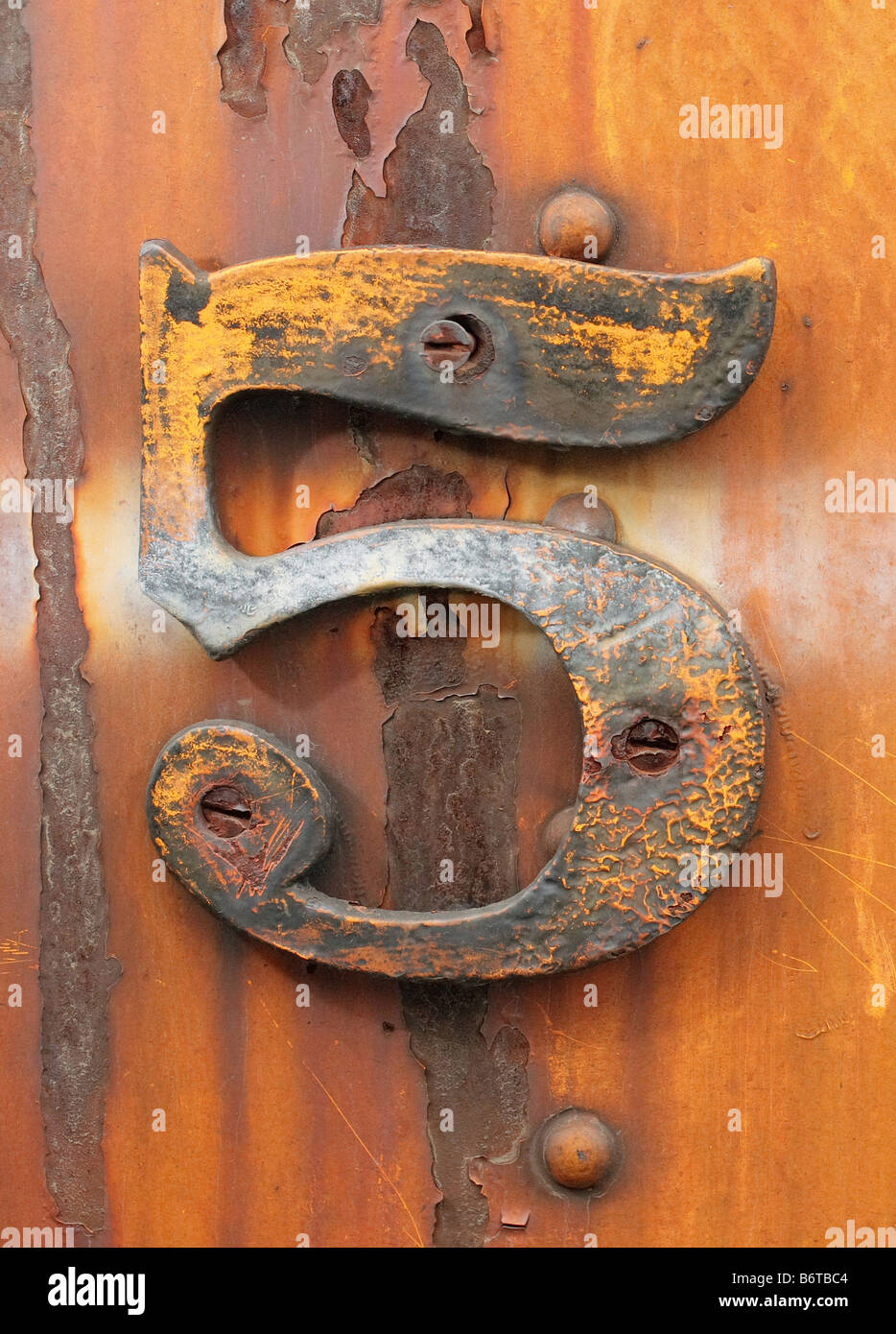 grungy number five affixed to rusty industrial metal - Stock Image
