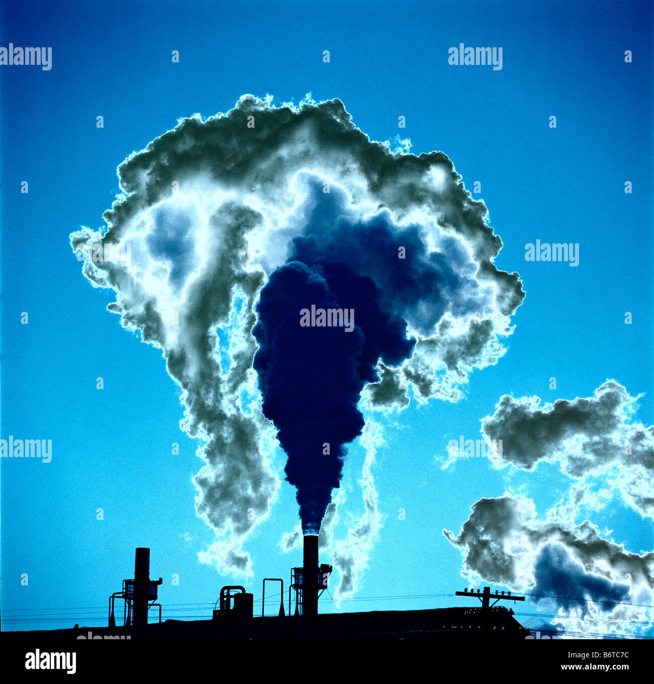 smoke pouring from chimney in industrial area - Stock Image