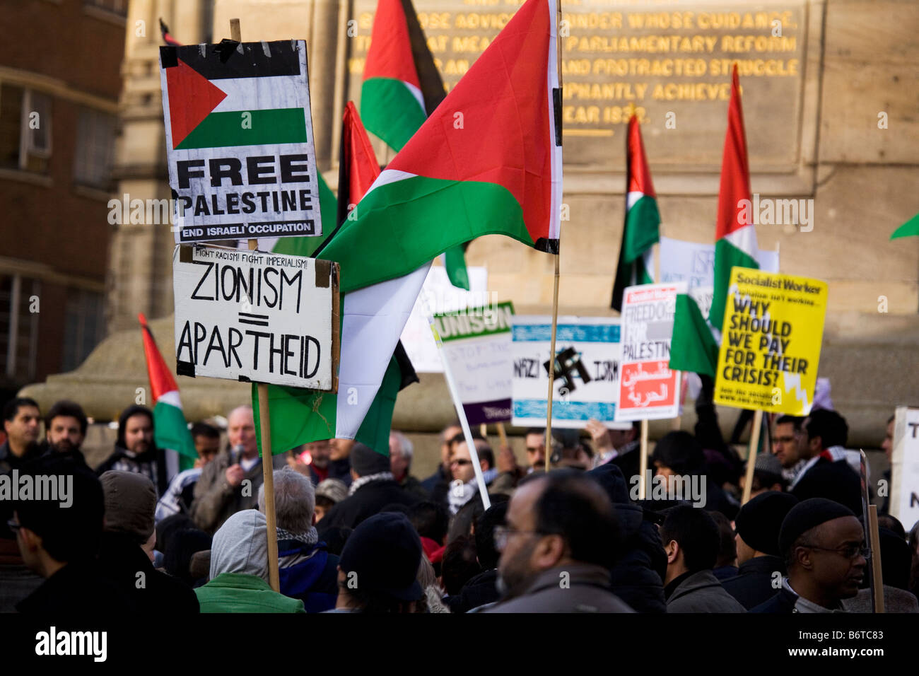 A placard at a demonstration in central Newcastle, England, compares Zionism to Apartheid. - Stock Image