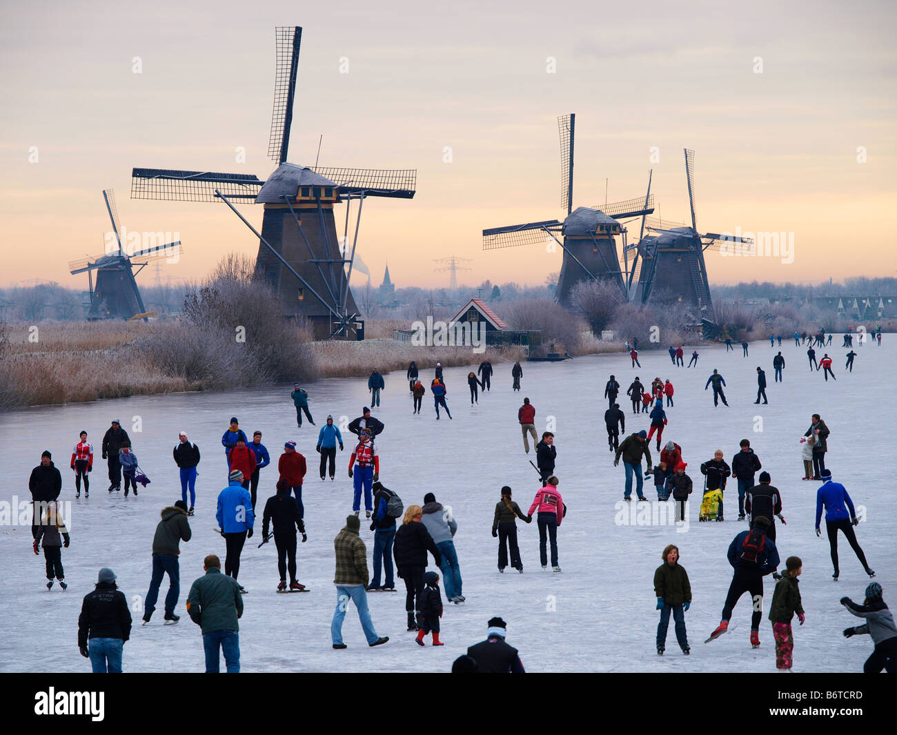 Winter in Holland many people skating on natural ice Kinderdijk windmills the Netherlands Stock Photo