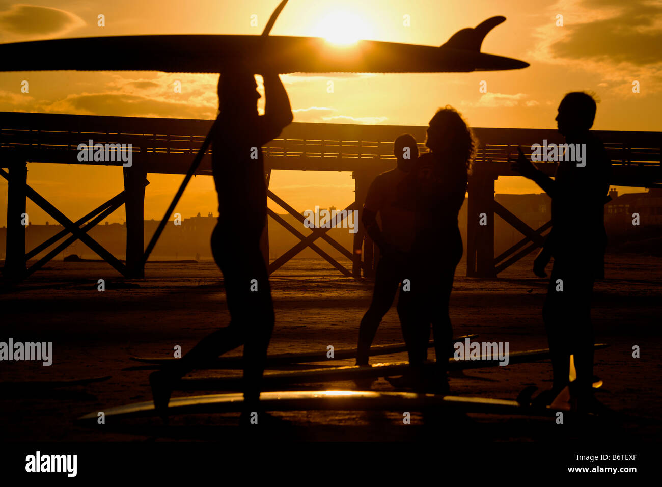 Surfers during sunset on the beach on Isle of Palms South Carolina - Stock Image