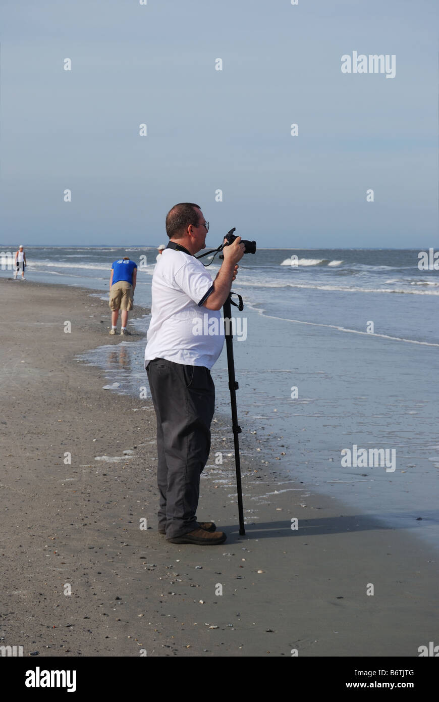 A middle aged overweight photographer prepares to take pictures of the Atlantic Ocean.  Photo by Darrell Young. - Stock Image