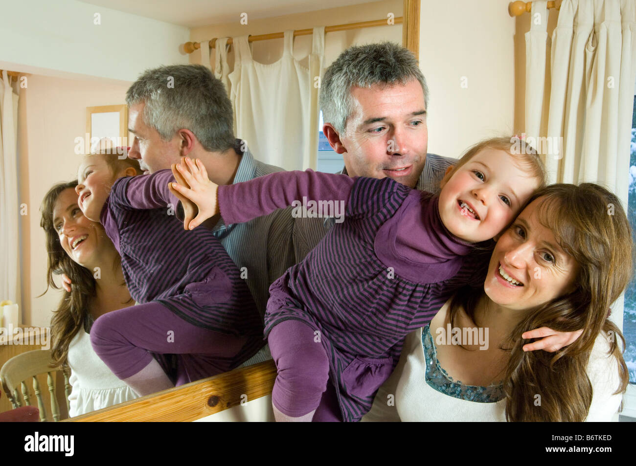 A scene of family life as parents pose with a wriggling toddler. - Stock Image