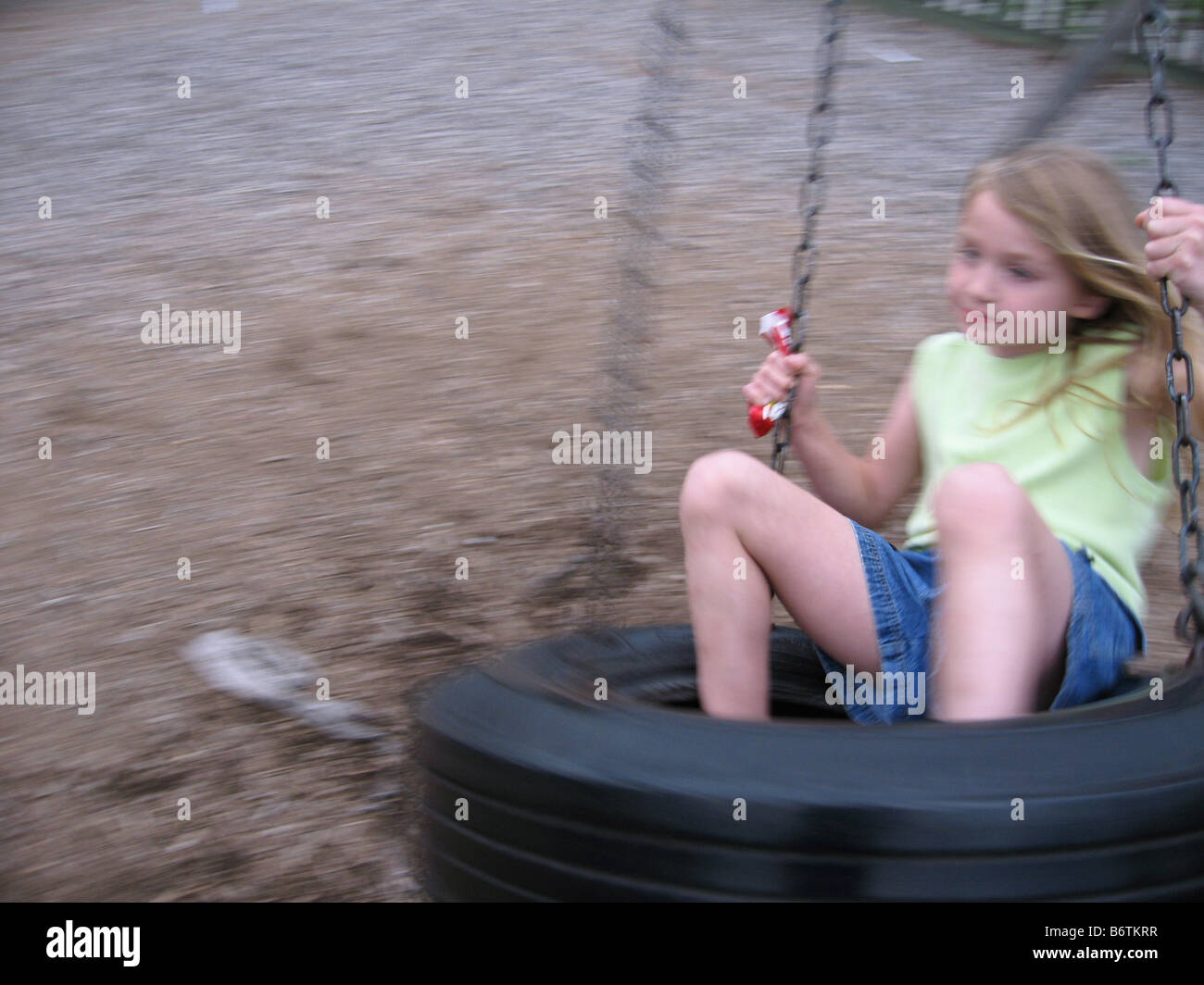 Little girl whirling around in a tire swing on a playground - Stock Image