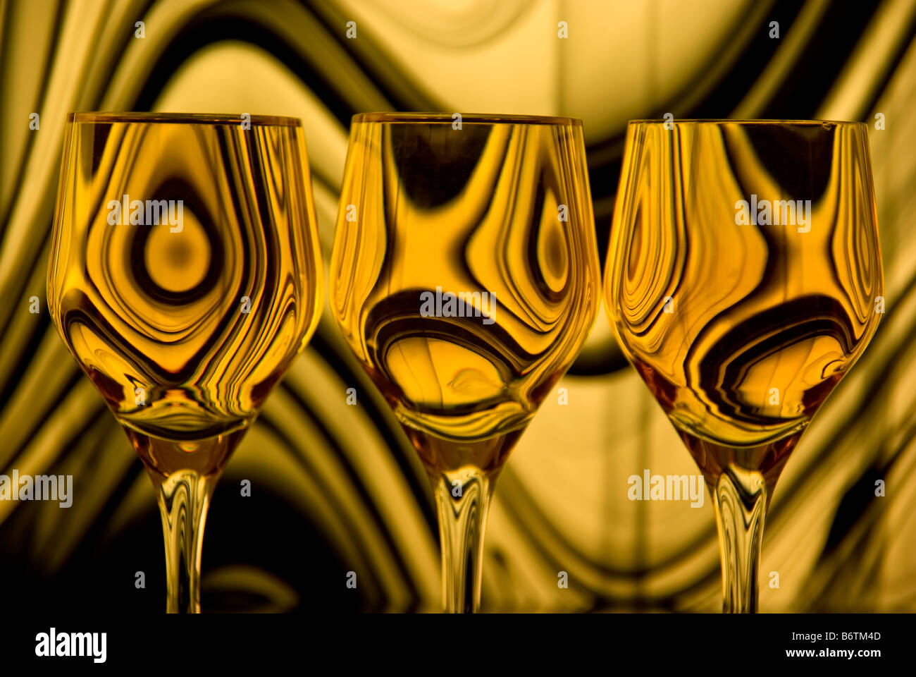 Close up of three wine glasses with a background of gold and black swirling lines reflected in each glass. Stock Photo