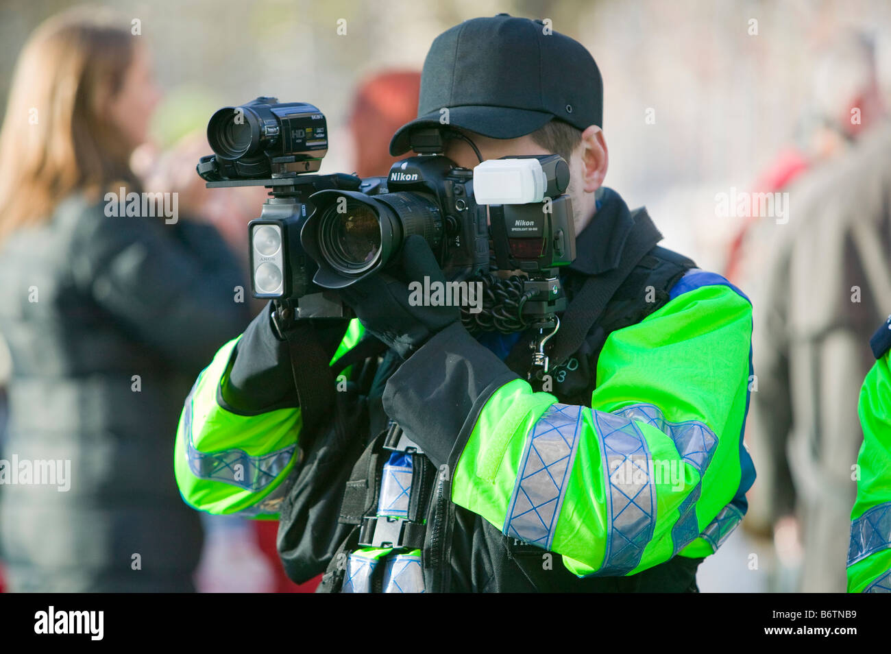 Police photographer photographing protestors at a climate change rally in London December 2008 Stock Photo