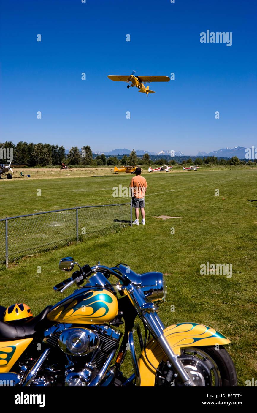 Man watching a yellow piper cub aircraft taking off at Piper