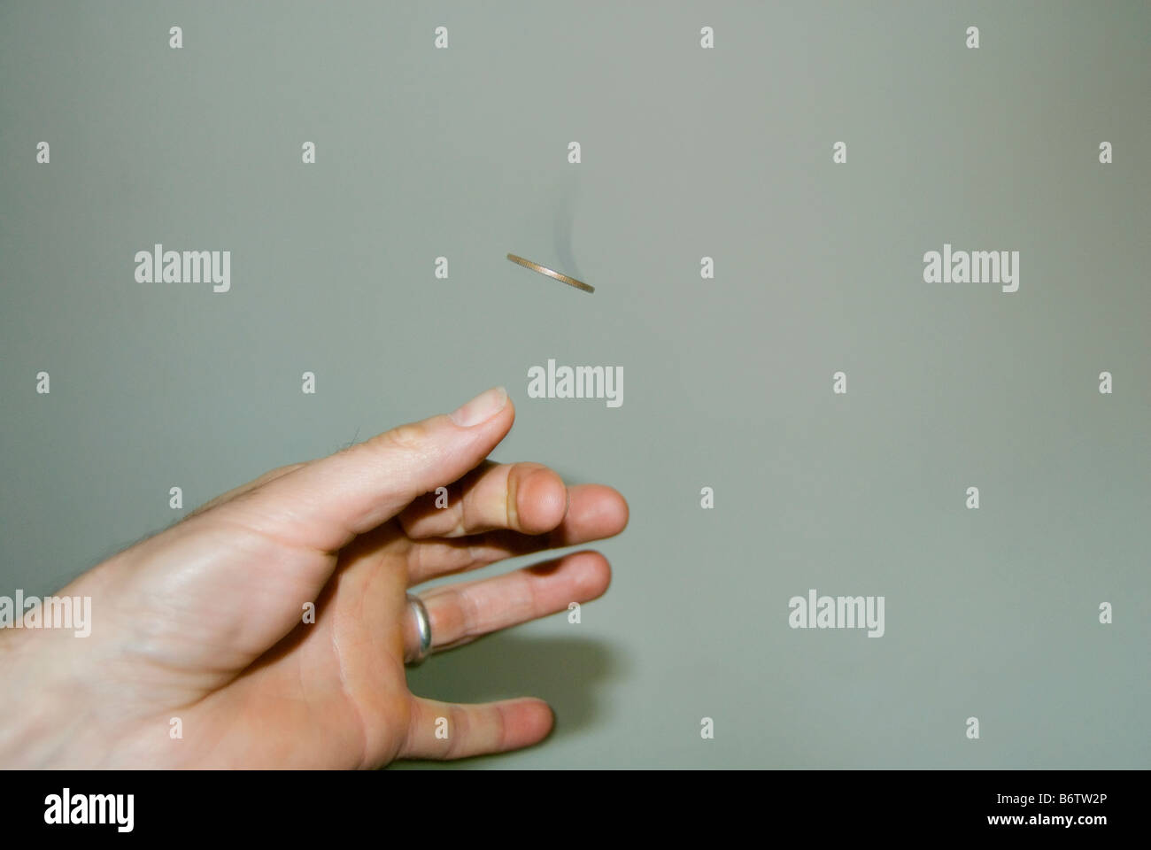 A coin flipped caught in mid air - Stock Image