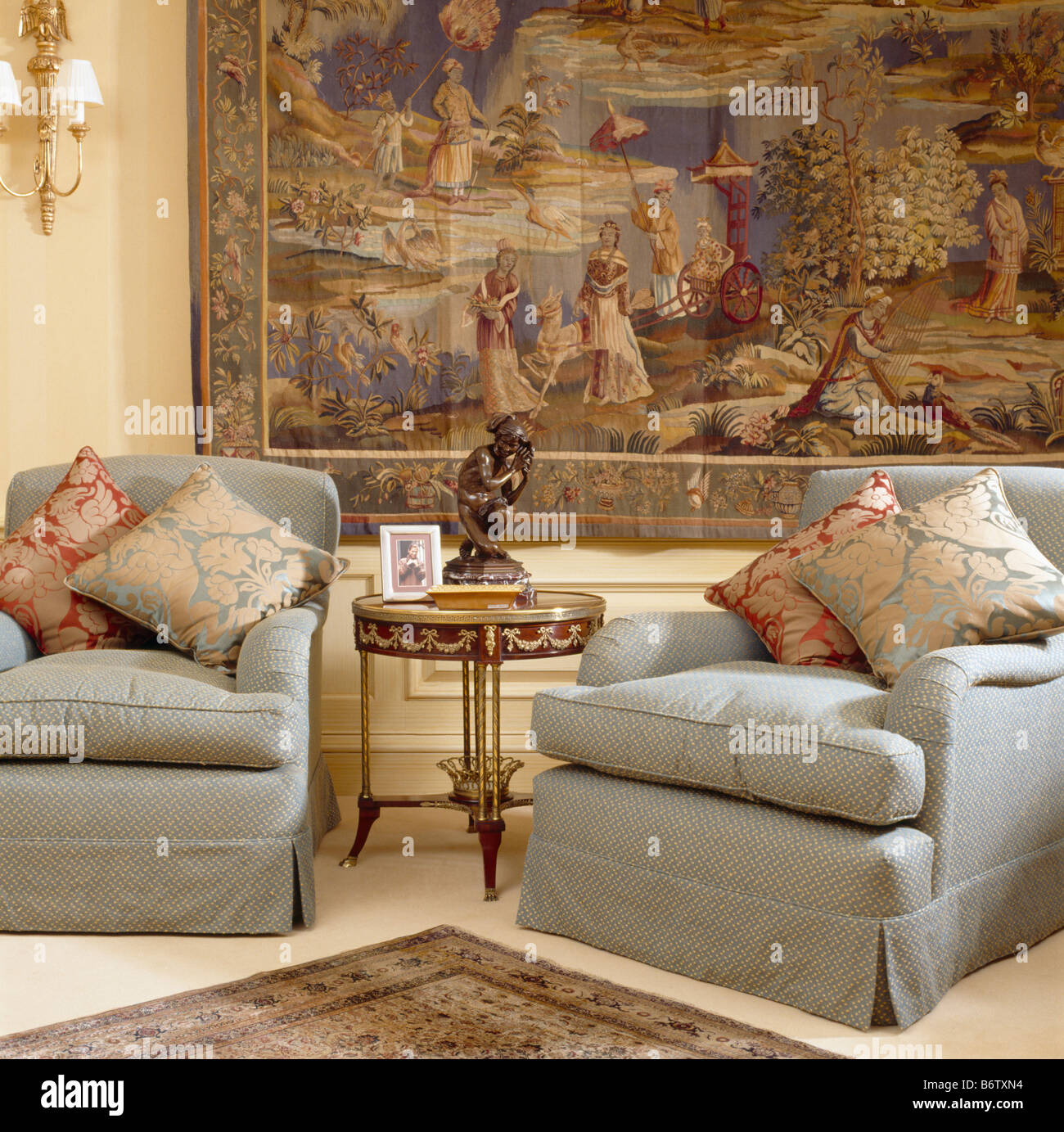 Patterned Silk Cushions On Comfy Grey Armchairs In Front Of Large Tapestry  On Living Room Wall