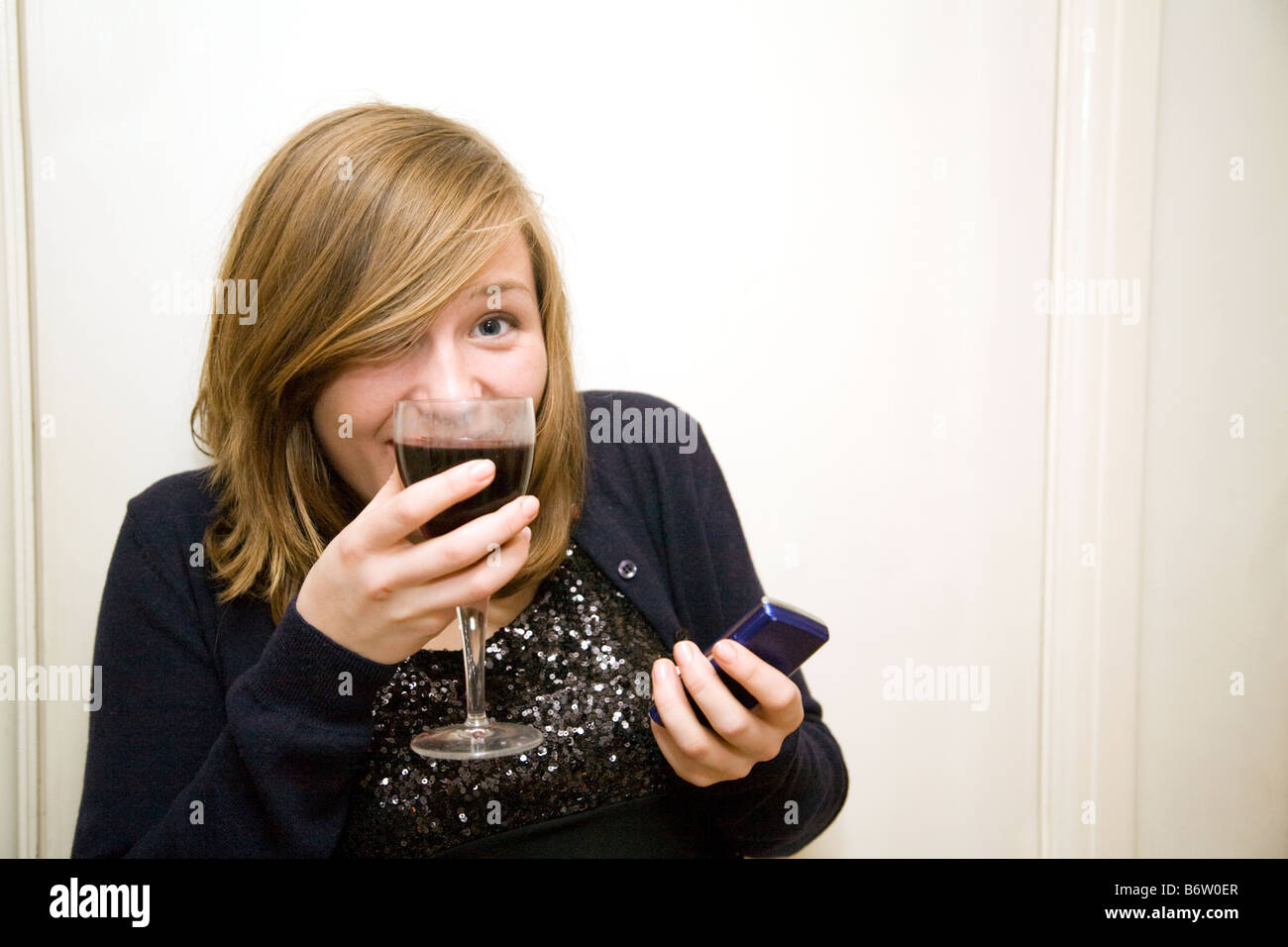 Blonde teenage girl age aged 14-15 years old drinking wine and texting with her mobile phone, UK - Stock Image
