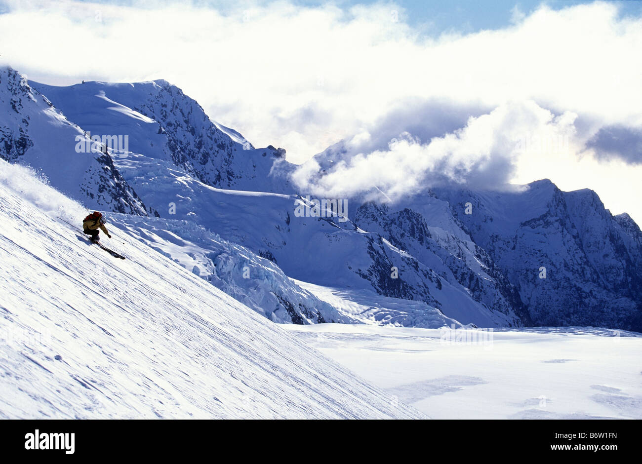 Skier turning an mountain slide with mountain back drop Franz Joseph glacier New Zealand - Stock Image