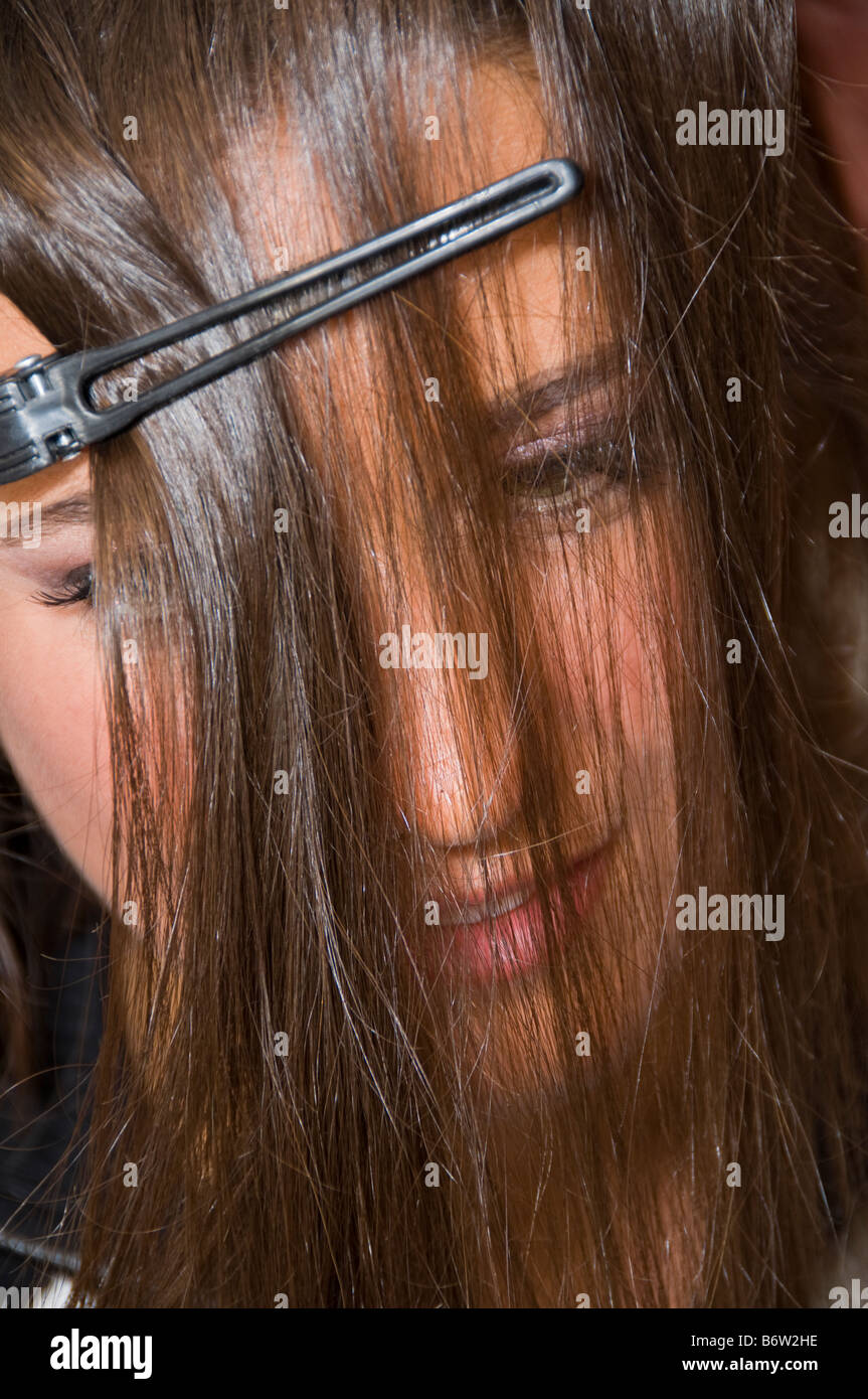 Woman getting hair done, close-up with hair over face. - Stock Image