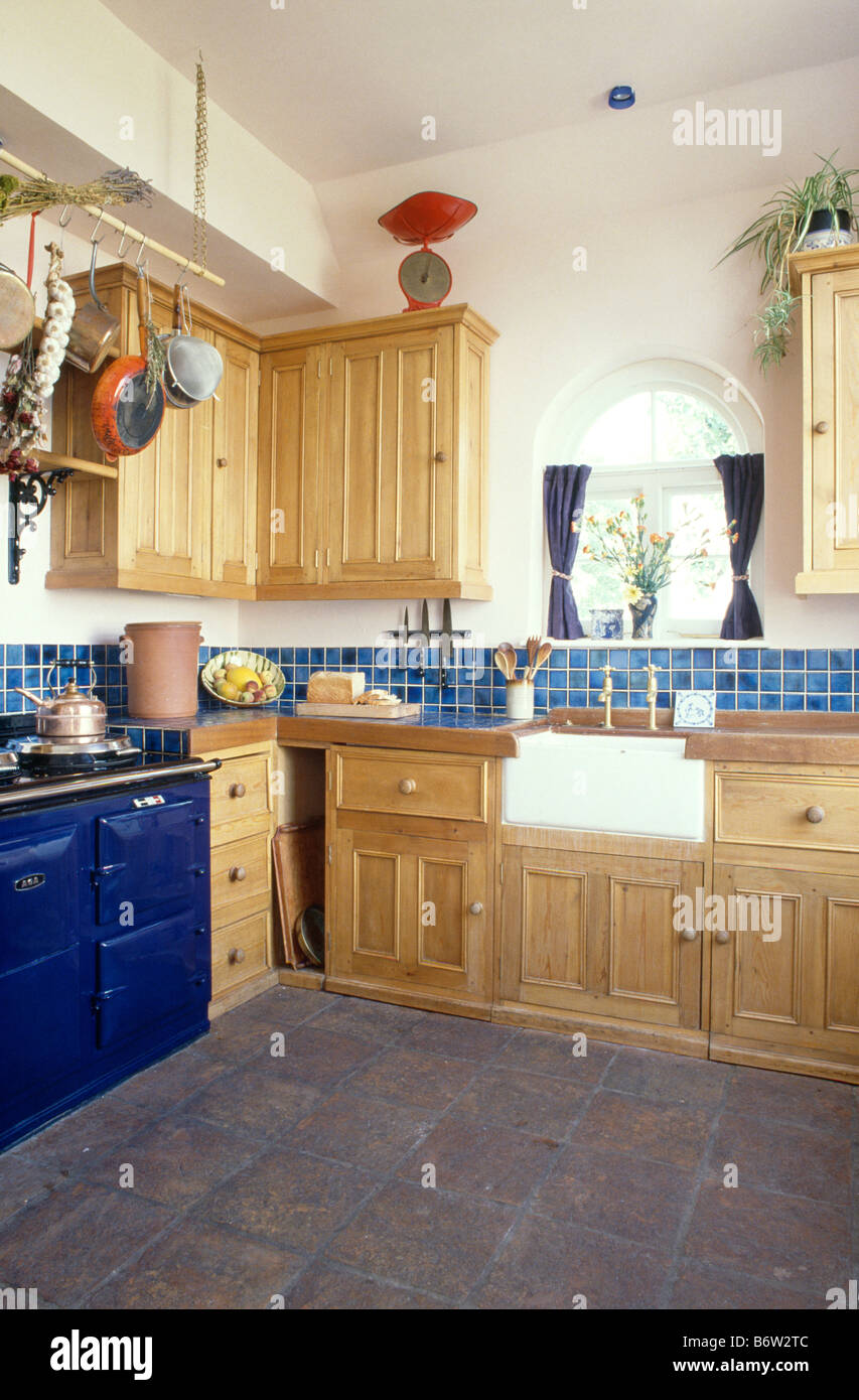blue aga in fitted pine kitchen with butlers sink and dark grey