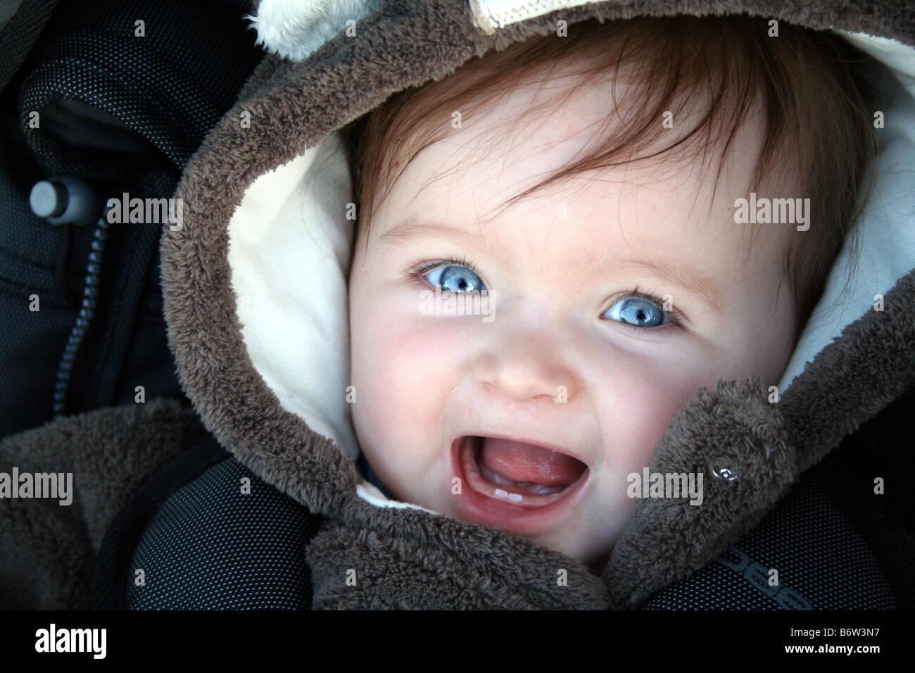 beautiful blue eyed brown haired baby smiling in pram