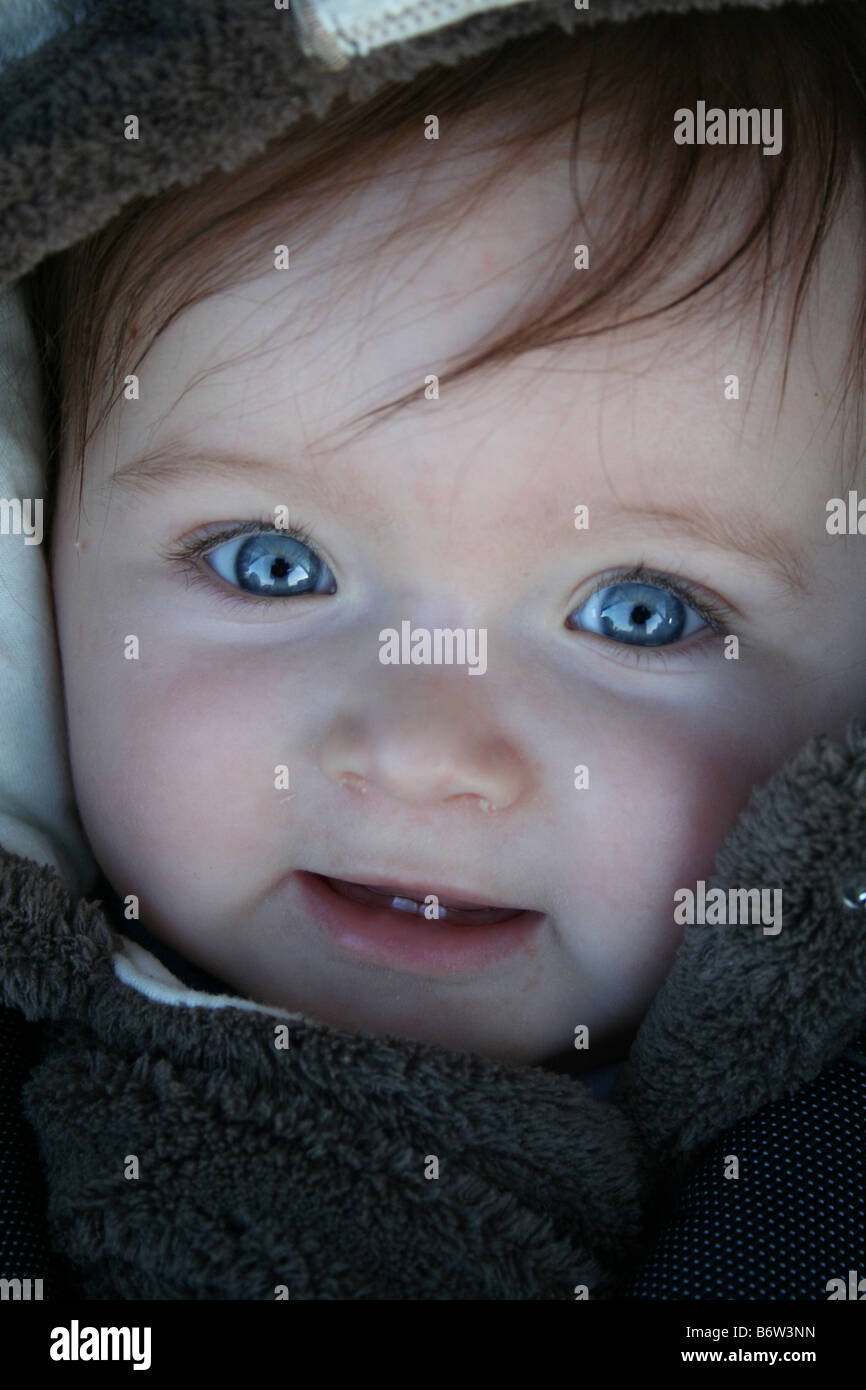 Beautiful Blue Eyed Brown Haired Baby Smiling in Pram - Stock Image