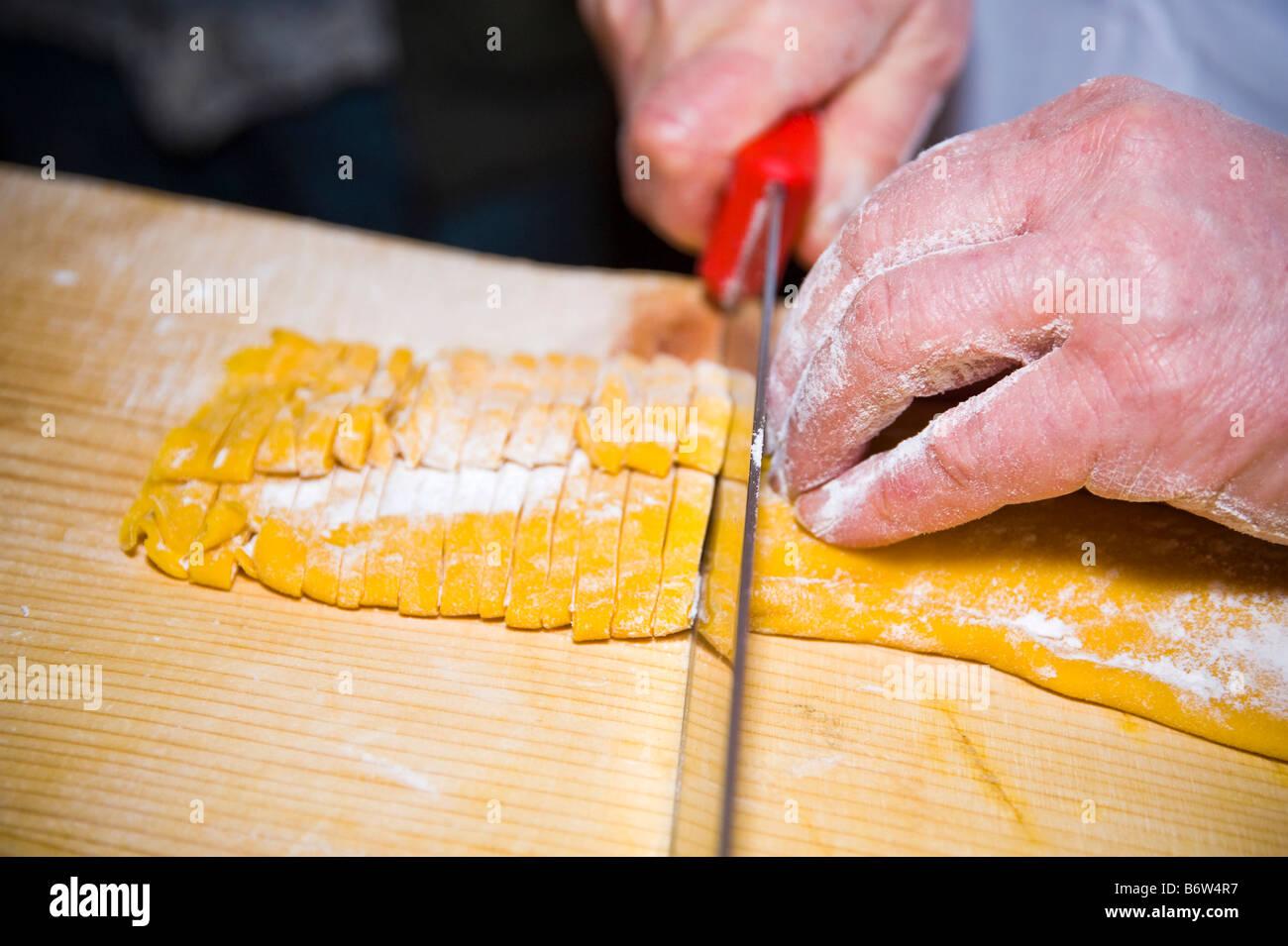 Cutting handmade fettuccine, close-up. - Stock Image