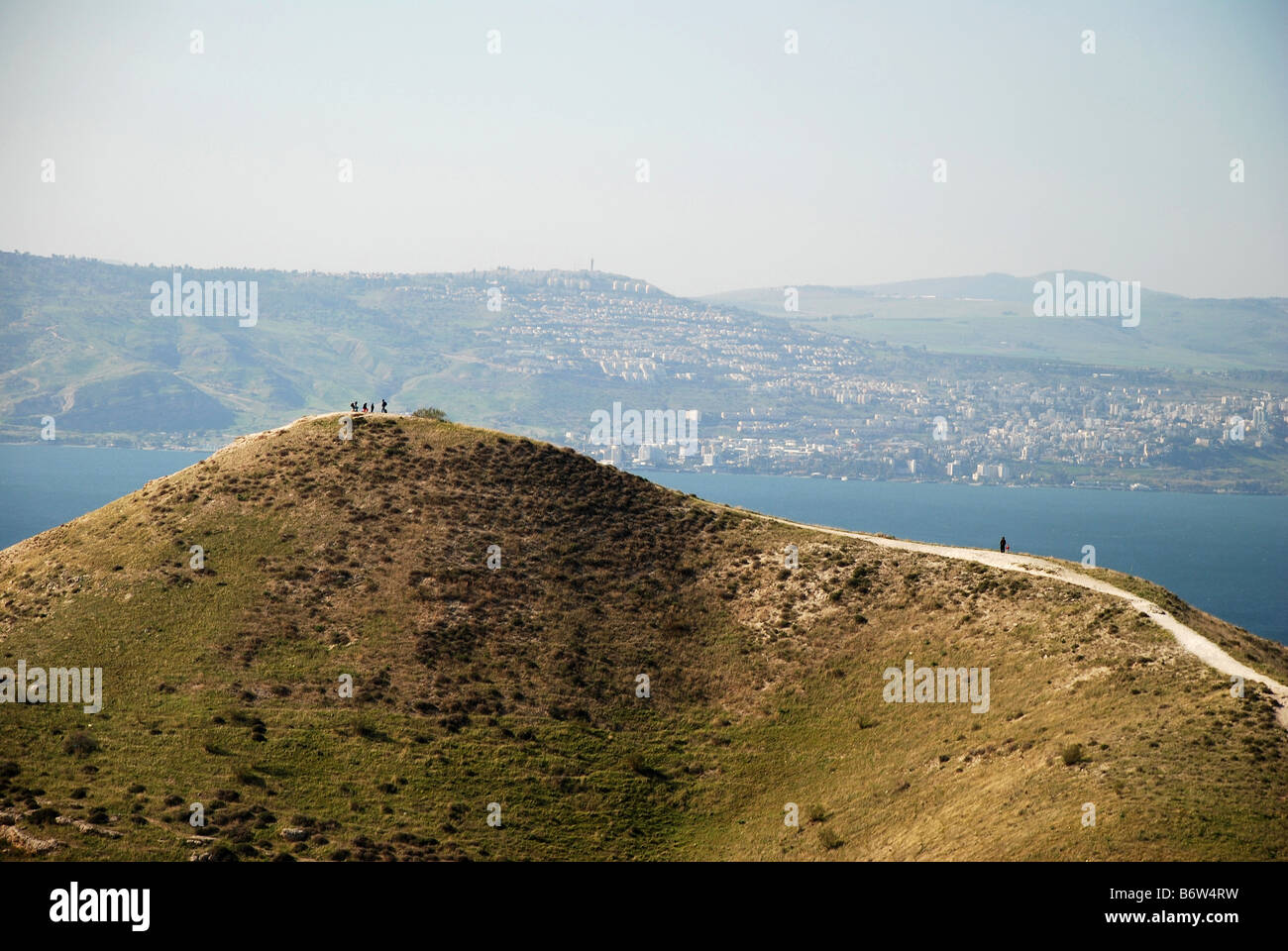 Inspirational view of hikers above the Golan mountain plateau over looking the Sea of Galilee. Stock Photo