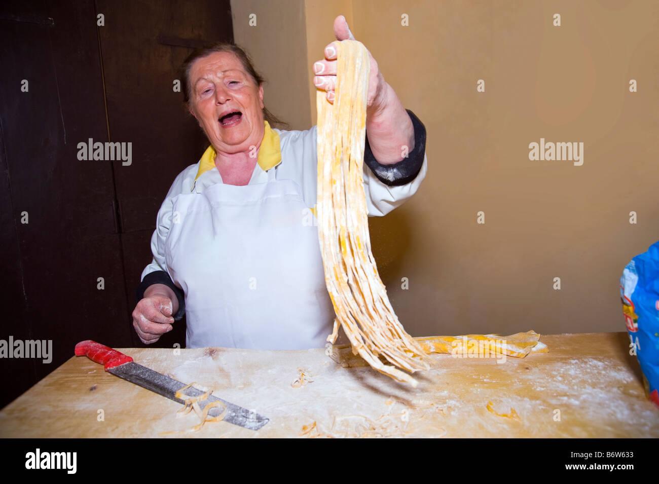Woman holding handmade pasta fettuccine. - Stock Image