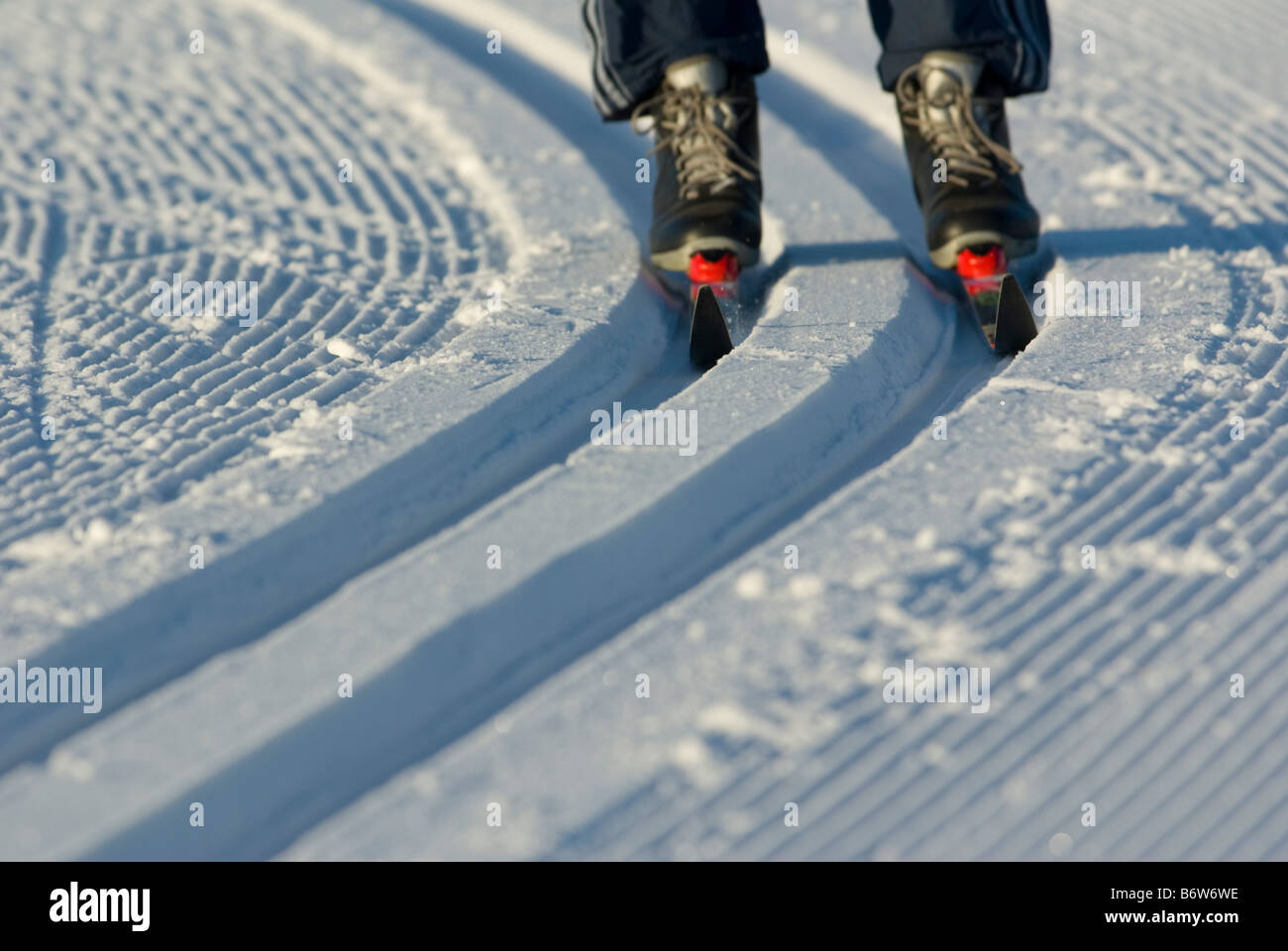 Skier on piste photographed so that only skis and ski boots are seen - Stock Image