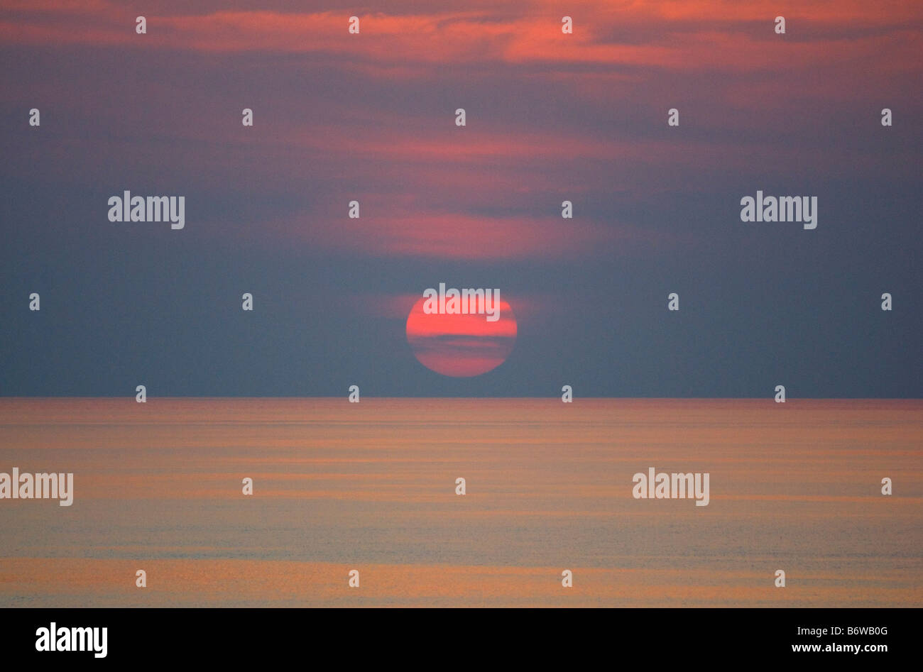 LARGE RED SUN SETTING ON SEA WITH CLOUDS - Stock Image