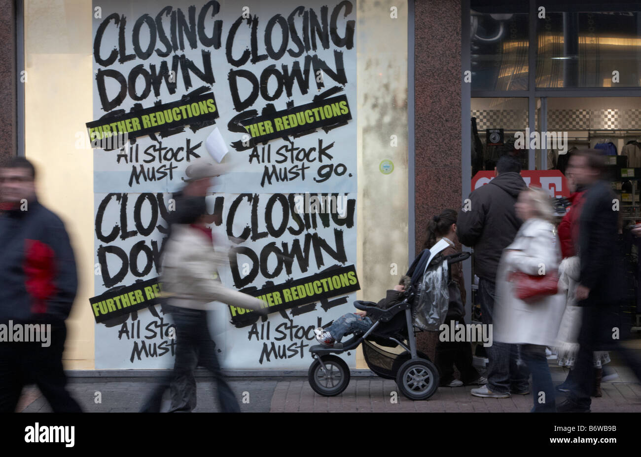 shoppers and families walking past closing down sale signs in a shop window in the uk - Stock Image
