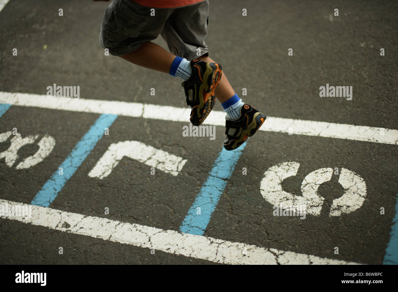 Children play hopscotch in a school playground - Stock Image