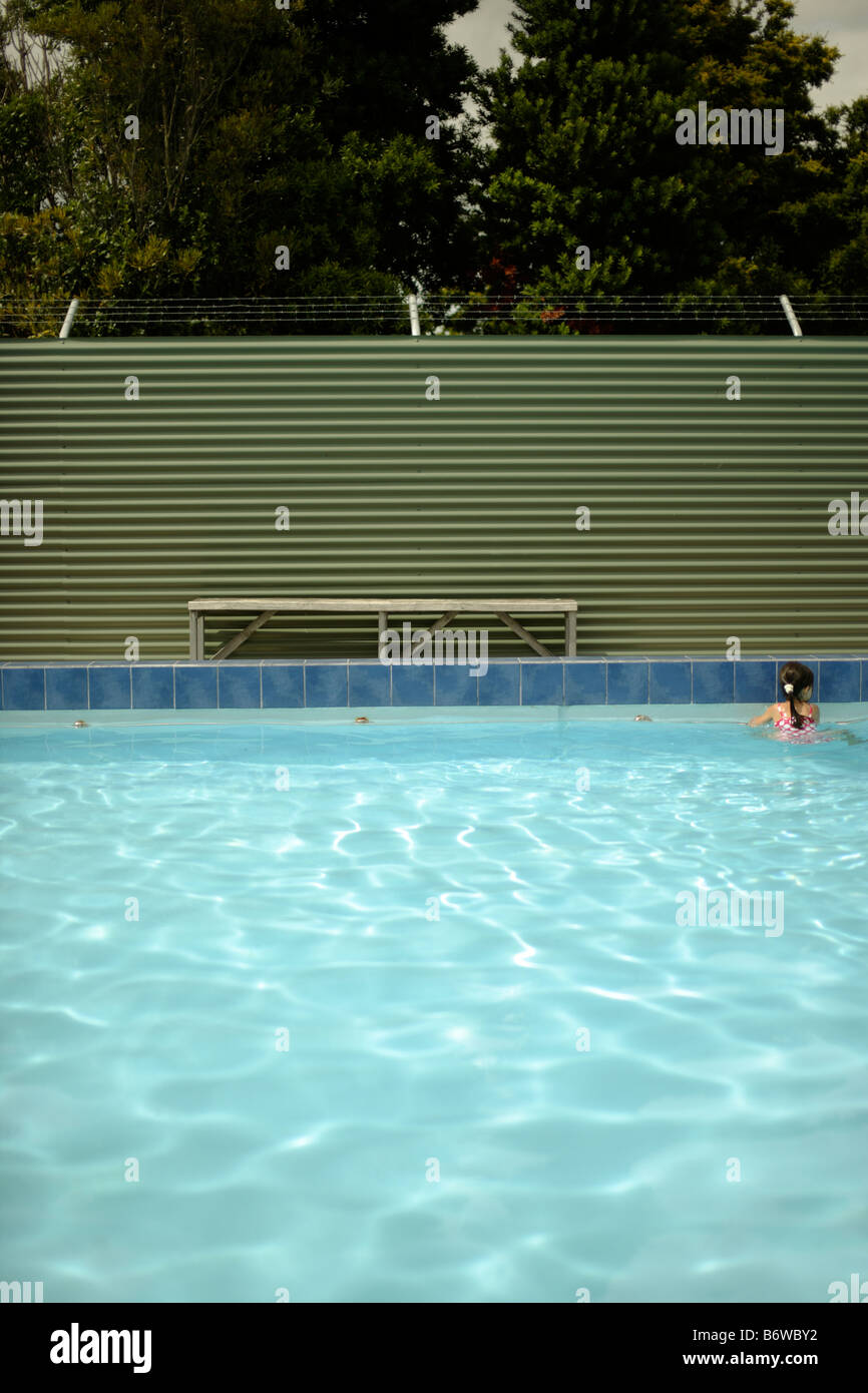 Five year old girl alone in pool holding rail in deep end - Stock Image
