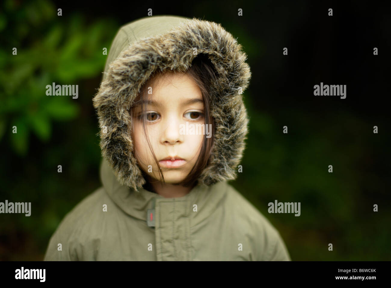 Child wears Parka coat with hood zipped up Girl aged five years - Stock Image