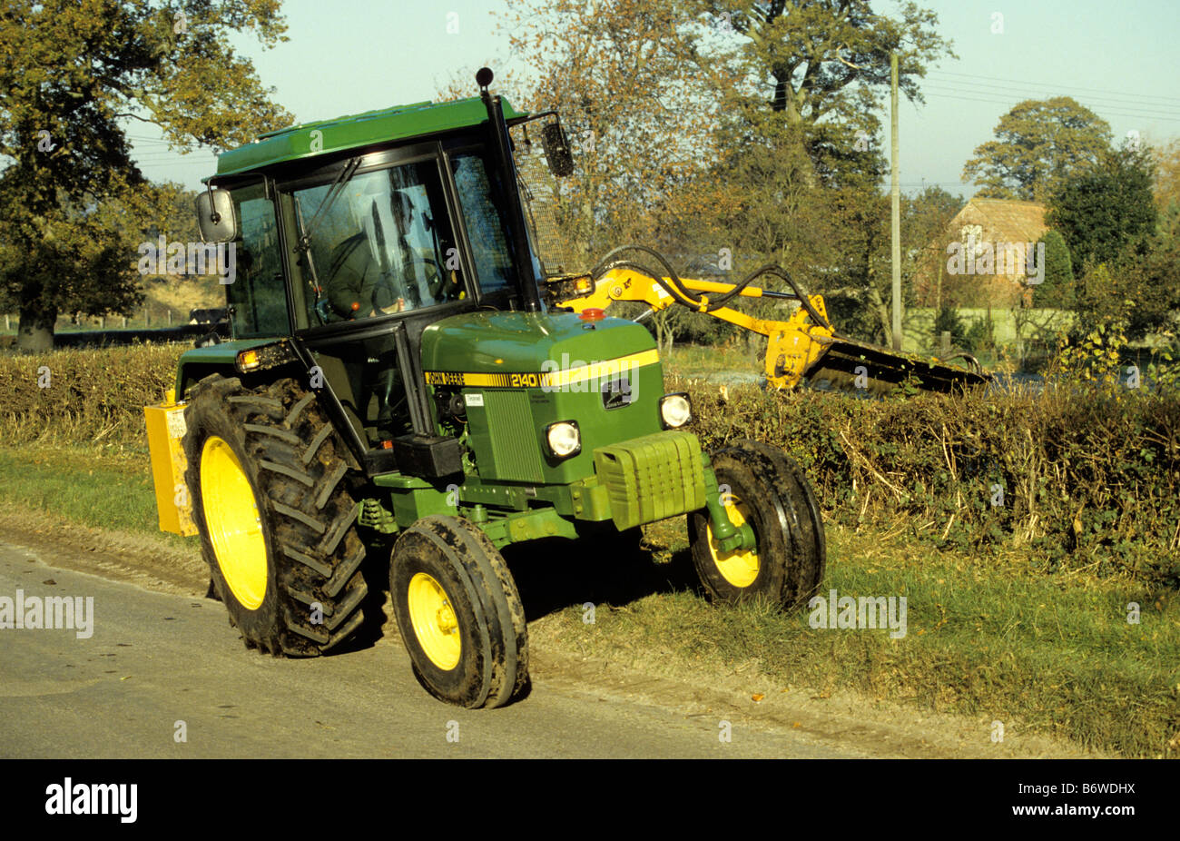 Farmer flailing hawthorn hedge / John Deere 2140 Tractor, Wiltshire, UK.