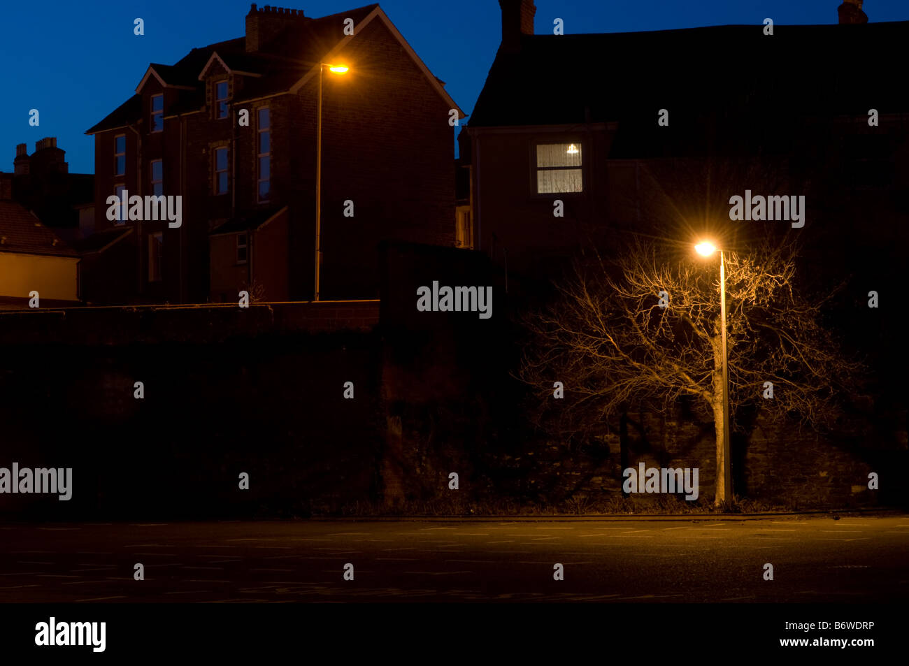 Houses and street lamps at night - deserted empty street scene in a town, UK - Stock Image