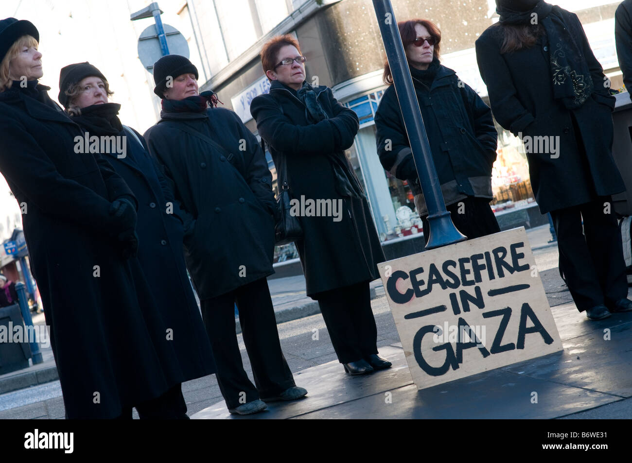 A group of concerned women dressed in black holding a public vigil  in Aberystwyth Wales UK calling for ceasefire - Stock Image