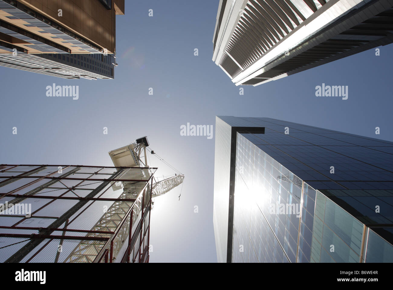 Worm's eye view of crane and skyscrapers - Stock Image