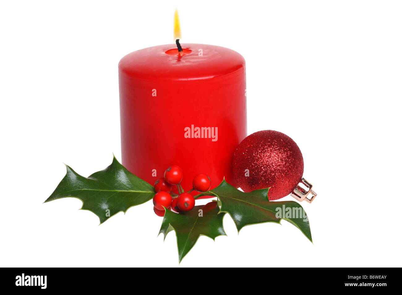 Christmas candle with holly and ornament cut out isolated on white background - Stock Image