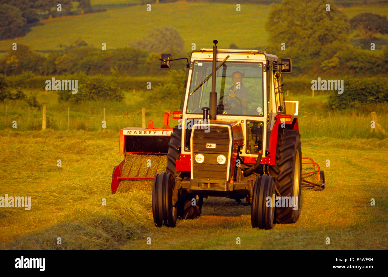 Farmer with old Massey Ferguson 690 Tractor and 124 Hay Baler, Wiltshire,  UK.