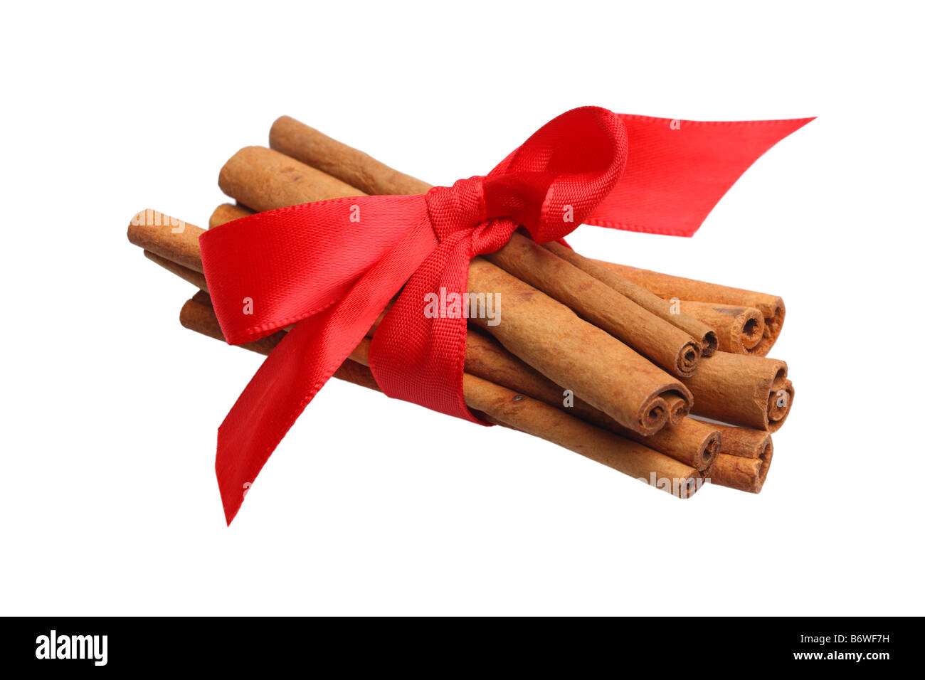 Cinnamon sticks tied with red ribbon cut out isolated on white background - Stock Image