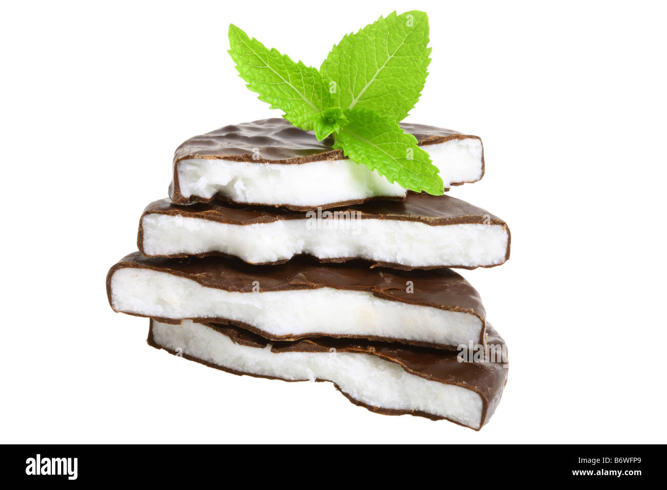 Stack of peppermint candy and fresh mint leaves cut out isolated on white background - Stock Image