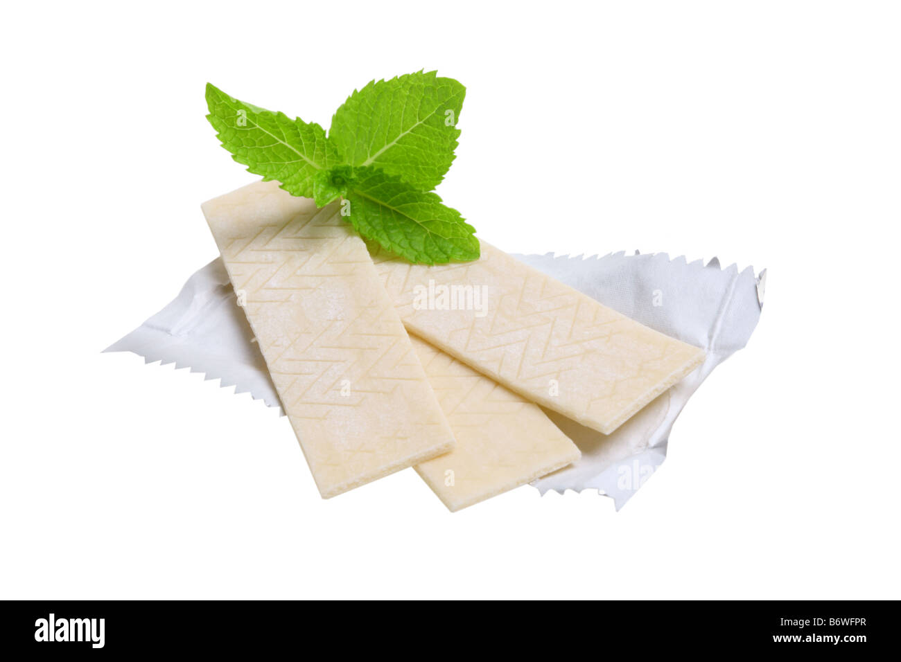 Chewing gum and mint leaves cut out isolated on white background - Stock Image