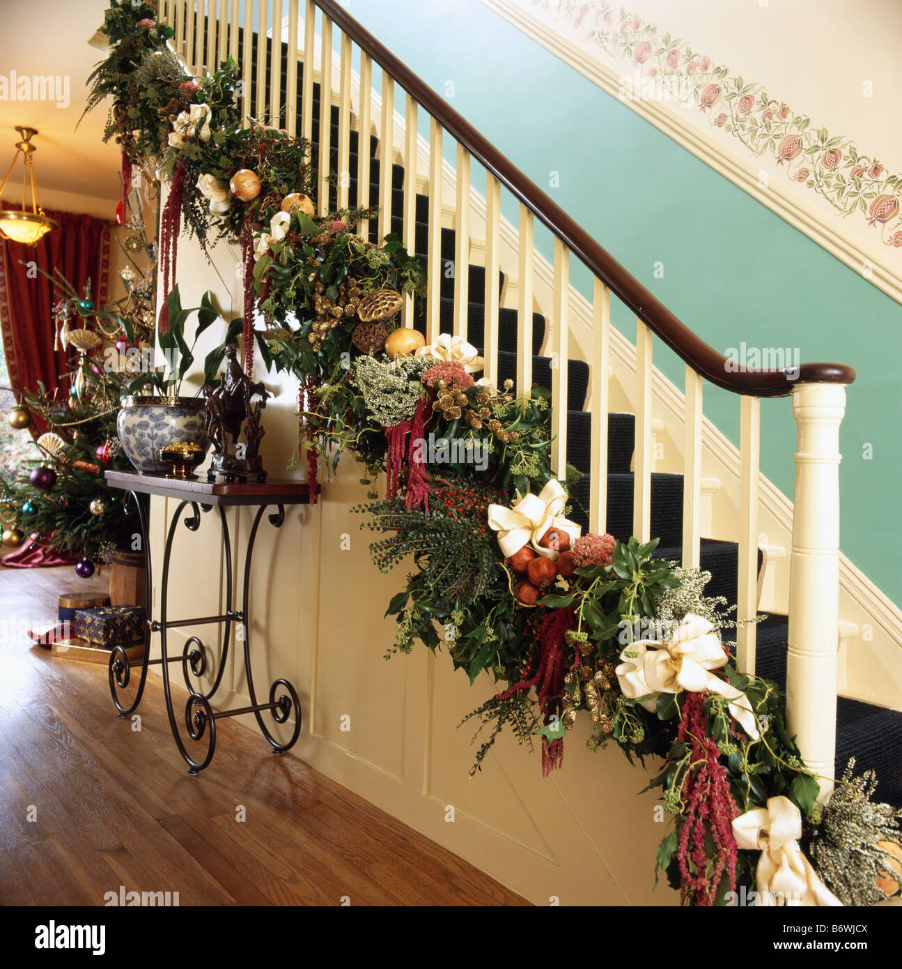 christmas garland of fresh foliage and red ribbons on bannisters of staircase in traditional hall with