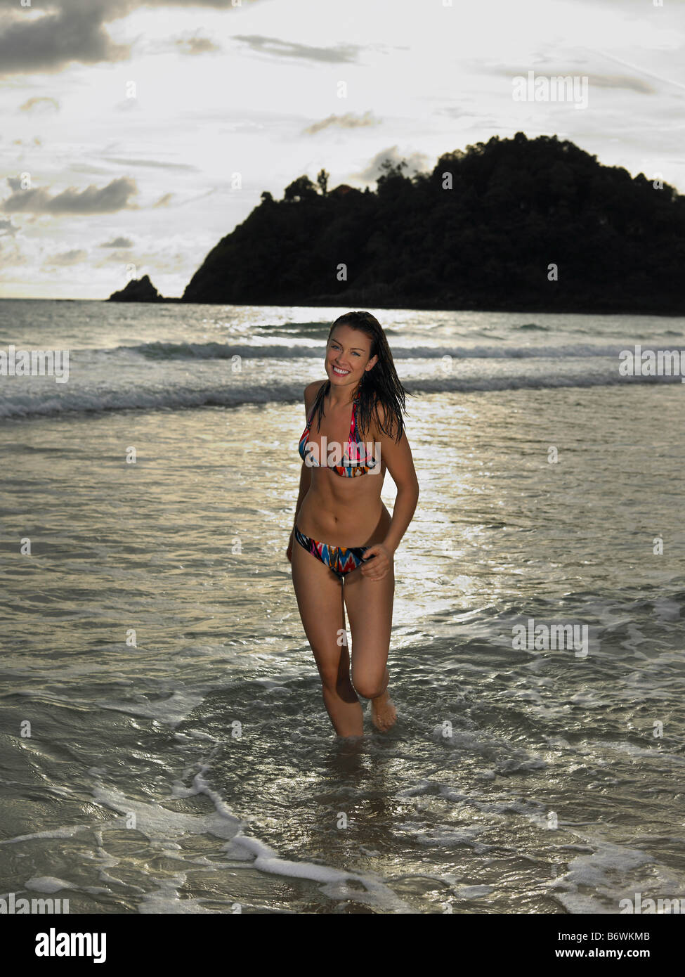 Young Woman Wading in Ocean at Sunset - Stock Image