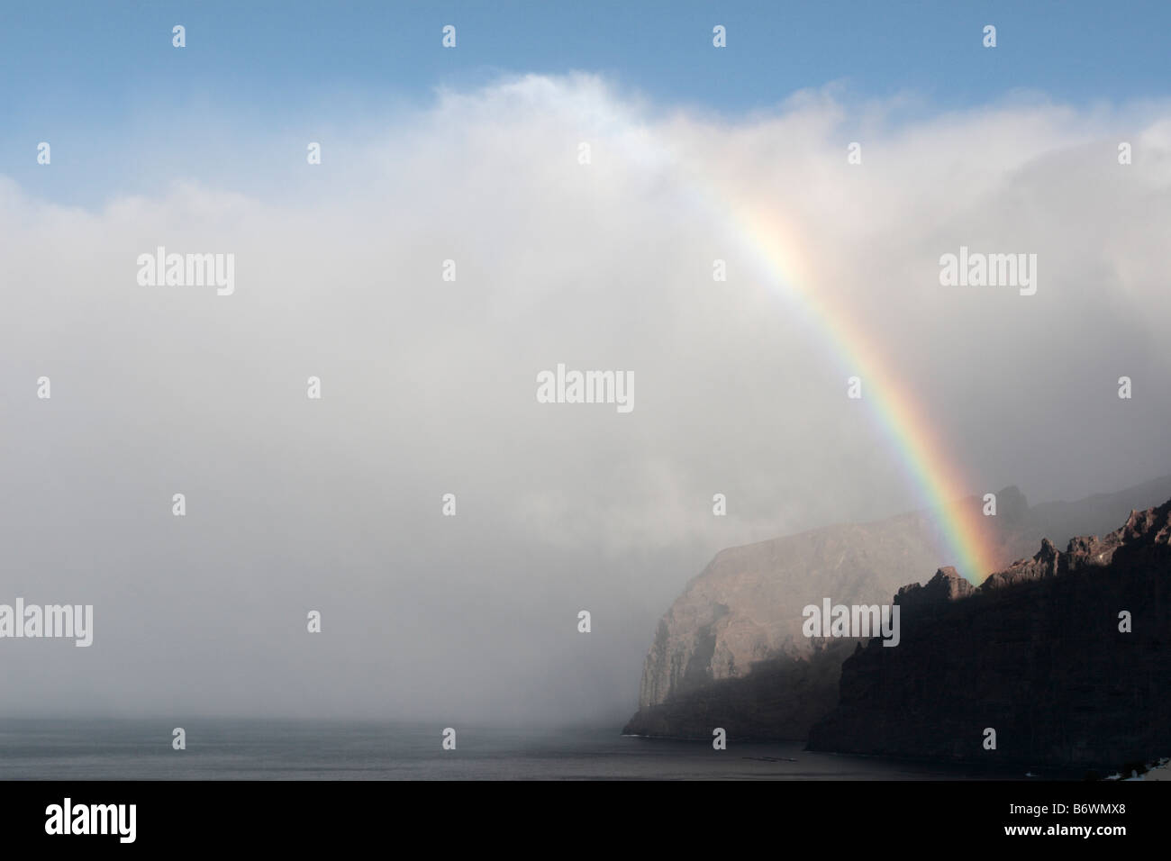 A rainbow during an early morning shower above the cliffs of Los Gigantes Tenerife Canary Islands Spain - Stock Image