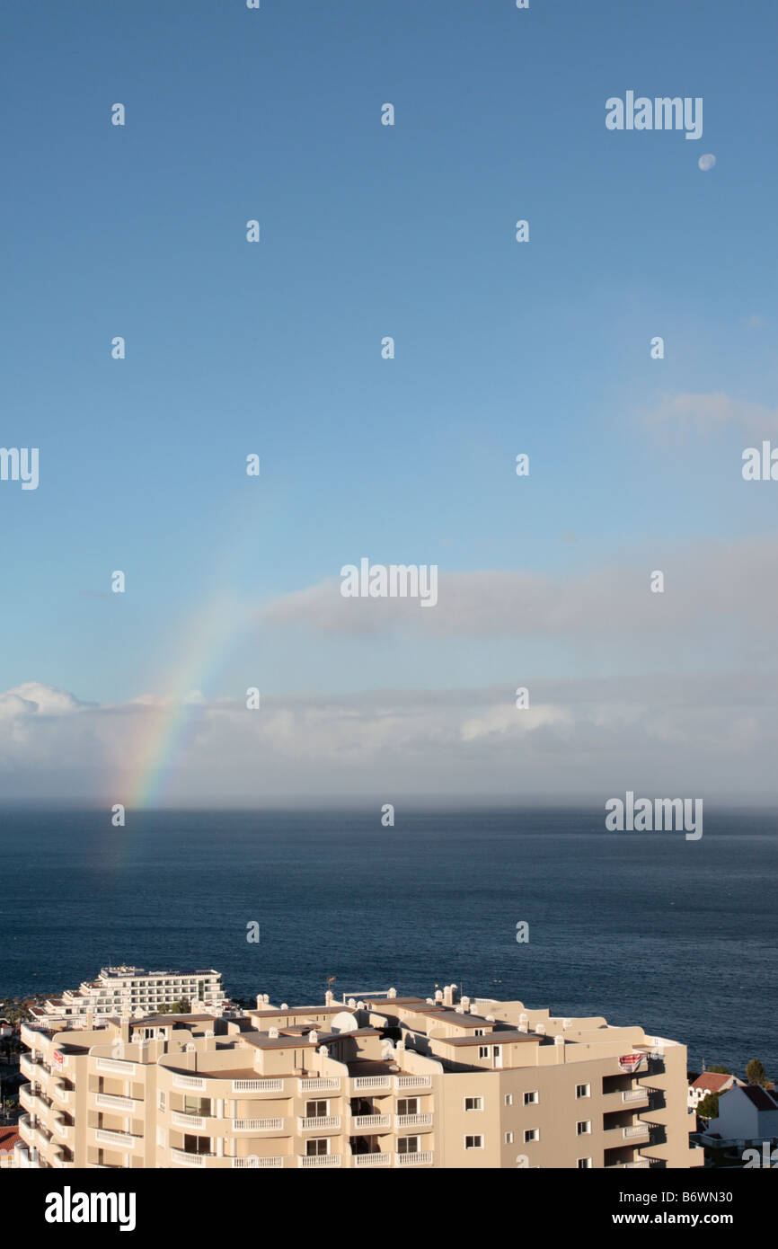 A rainbow at sea off the coast of Tenerife with the hotel Barcelo Santiago and a large apartment block in the foreground - Stock Image